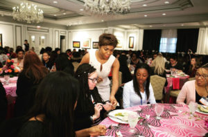 Confidence Coach Jacqueline M. Baker helping a teenage girl learn from mistakes in dining etiquette